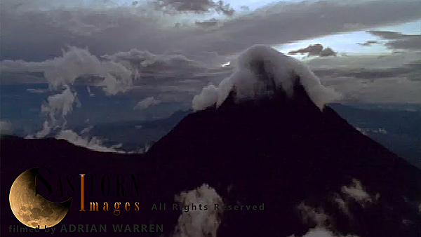 Forward tracking aerial shot, Virunga volcanoes, camera approaches cloud topped peak of Mt Mikeno over low broken cloud, with thunderstorm in background. Camera passes close to the left of the peak of Mt Mikeno revealing distant, smoking silhouette of Niragongo