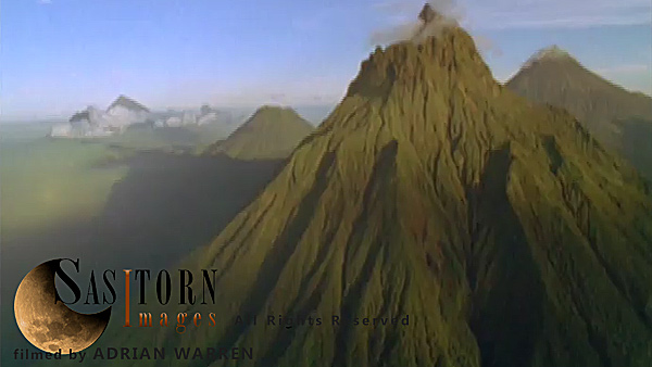 Forward tracking aerial shot, Virunga volcanoes in late afternoon sun. Camera approaches Mt Mikeno in foreground, with Mts Karisimbi and Visoke (Bisoke) behind and Mt Sabyinyo in distance