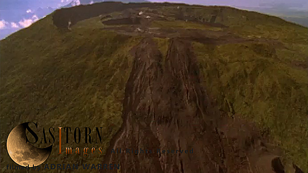 Forward tracking aerial shot, Virunga volcanoes, camera passes over old lava flow / cinder plains towards crater of Nyamuragira (Nyamulagira), camera passes over crater with steaming vents to reveal smoking, silhouetted Nyiragongo