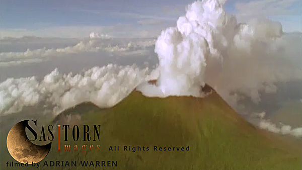 Forward tracking aerial shot, Virunga volcanoes, camera approaching smoking crater of Mt Nyiragongo surrounded by light broken of cloud in morning sun, camera tilts down over crater looking down through light broken cloud and tilts back up to horizon