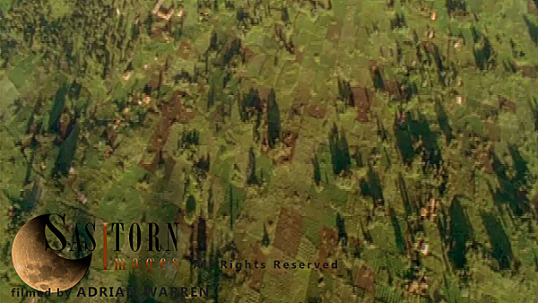 Forward tracking aerial shot, Rwandan countryside, camera tilted down, passing over field patterns and trees in late afternoon sun.