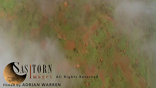 Forward tracking aerial shot, Rwandan countryside, camera tilted down looking through broken cloud in valleys showing countryside below, camera passes low over hill tops