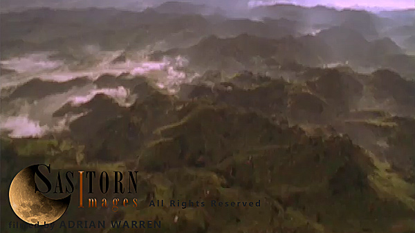 Forward tracking aerial shot, Rwandan countryside, camera passes high over misty valleys with exposed ridges, backlit by morning sunlight, through high cloud