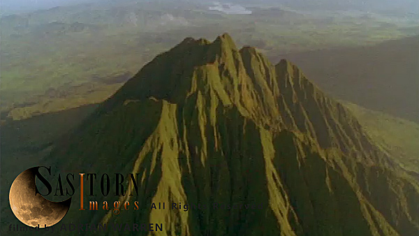 Forward tracking aerial shot, Virunga volcanoes. camera passing high over Mt Sabyinyo in morning sun, camera tilts down slowly as knife edge ridges fill shot, camera passes over summit tilting down over ridges with small wisps of cloud