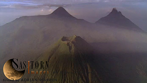 Forward tracking aerial shot, Virunga volcanoes, camera approaches Mt Visoke (Bisoke) in early morning sun with Karisimbi and Mikeno in background, camera passes high over Visoke (Bisoke), fully tilting down over crater lake and passing over to reveal open forest