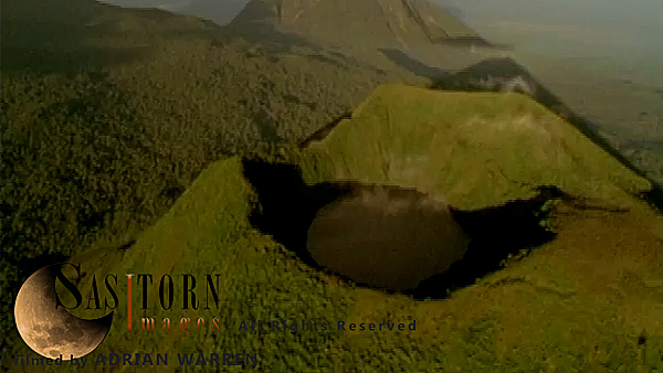 Forward tracking aerial shot, Virunga volcanoes, camera approaches Mt Visoke (Bisoke) with Mt Mikeno behind and Mt Karisimbi to left of shot, camera tilts down over crater lake and slowly tilts back up to show Mt Mikeno with cloud covered summit